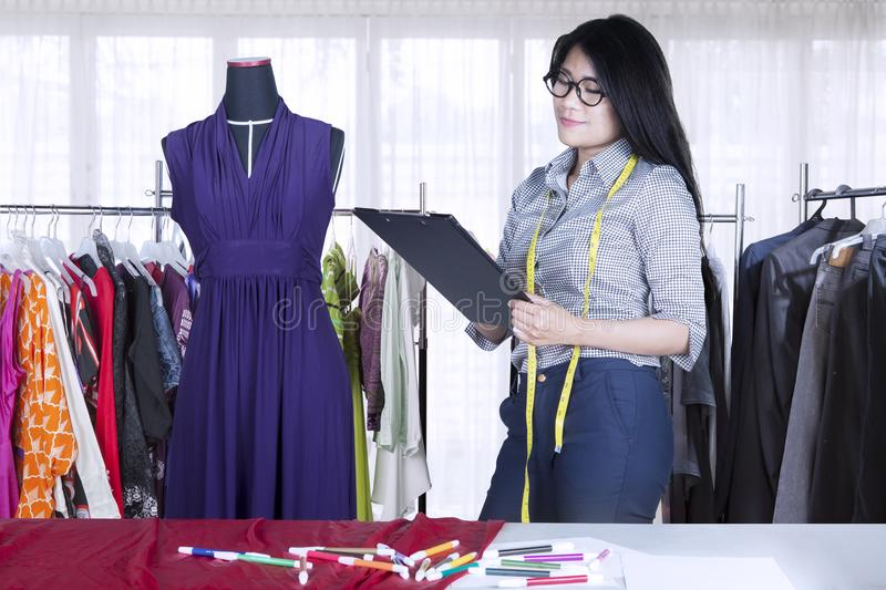Pretty seamstress working with a clipboard royalty free stock images