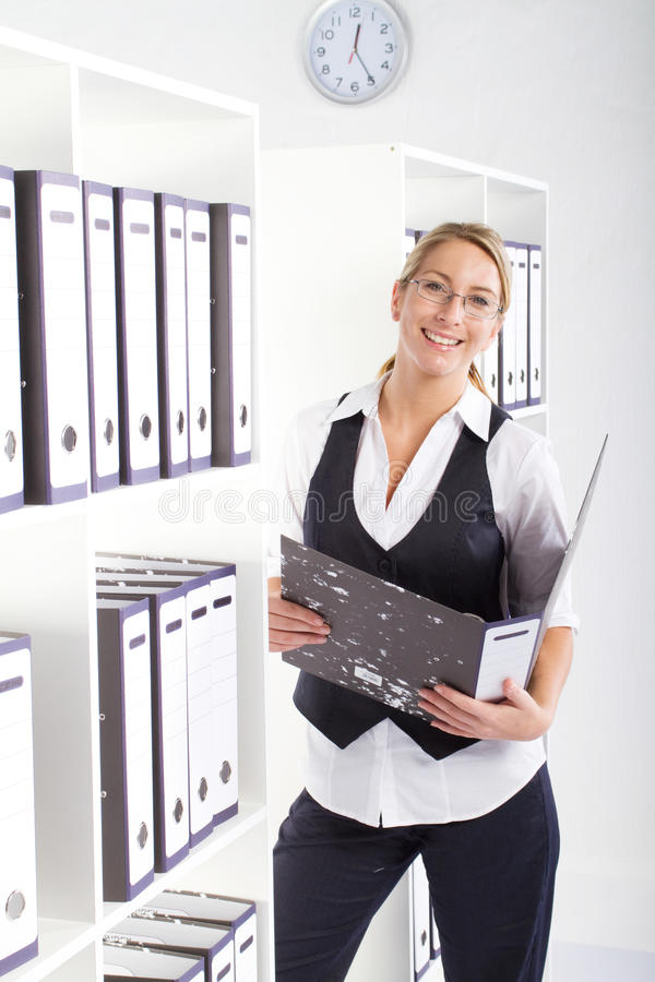 Pretty secretary. A pretty confident secretary dressed smartly looking for files in office bookshelf stock images