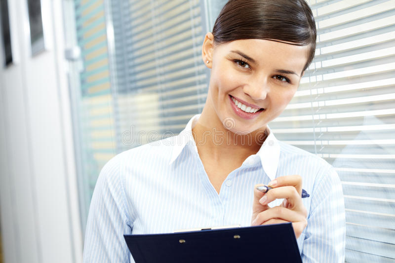Pretty secretary. Image of young pretty secretary holding pen and folder royalty free stock photography