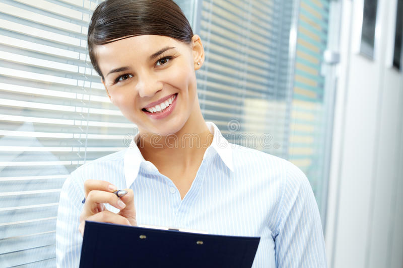 Pretty secretary. Image of young pretty secretary holding pen and folder royalty free stock images