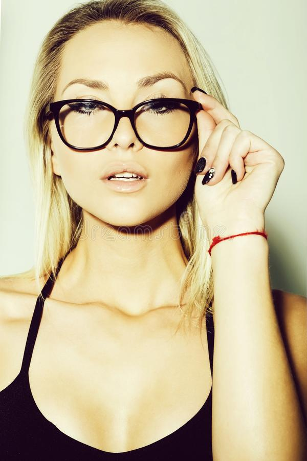 Pretty secretary girl or businesswoman in eyeglasses with blonde hair. Pretty secretary girl or businesswoman in cute stylish black eyeglasses with long blond royalty free stock photos