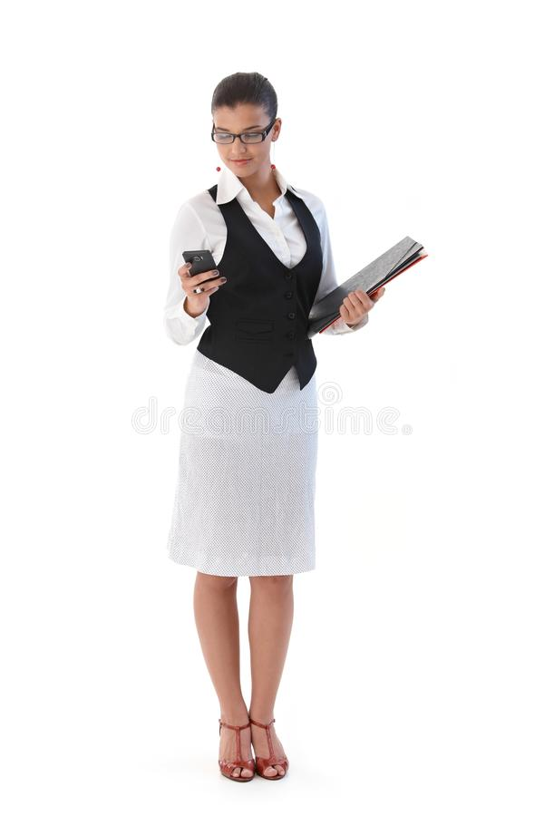 Pretty secretary with mobile and folders. Pretty secretary holding folders, using mobile phone royalty free stock photos