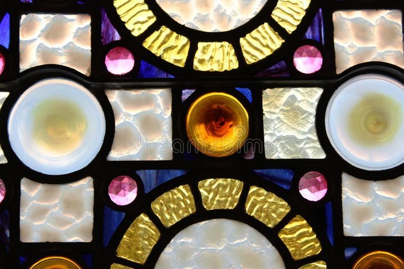 Pretty section of stained glass window in colors of yellow, blue, pink, and white. Background of pretty stained glass window with patterns and textures done in stock photo