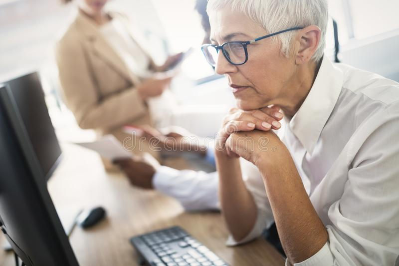 Pretty senior business woman, successful confidence in financial building. Pretty older business woman, successful confidence in financial building royalty free stock images