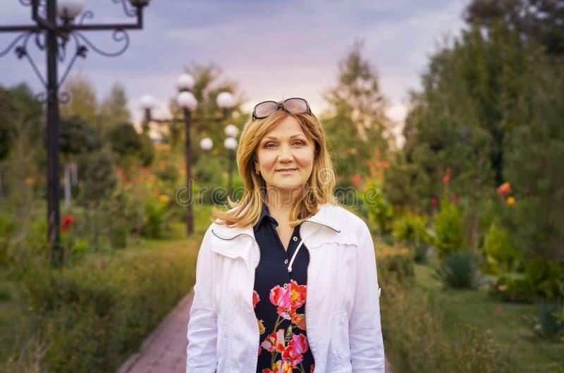 A pretty senior woman in a beautiful park stock photo