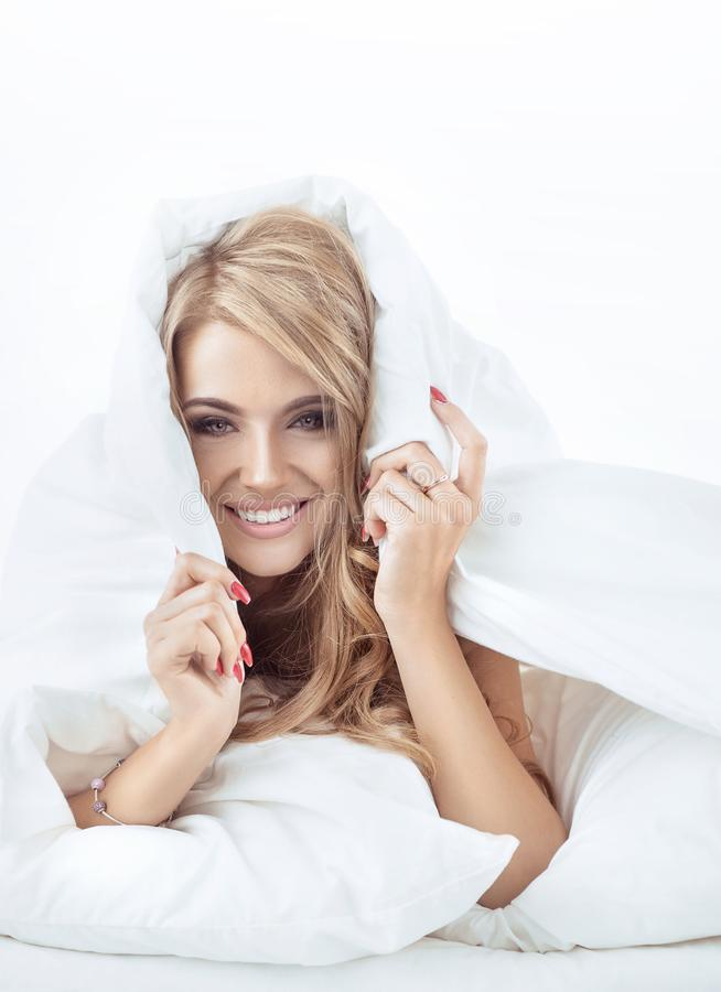 Pretty, sensual blonde relaxing in the bright bedroom royalty free stock photos