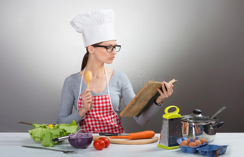 Pretty serious woman cooking with old cookbook. Portrait of a pretty serious woman in chef's hat cooking with old cookbook, on gray background stock photos