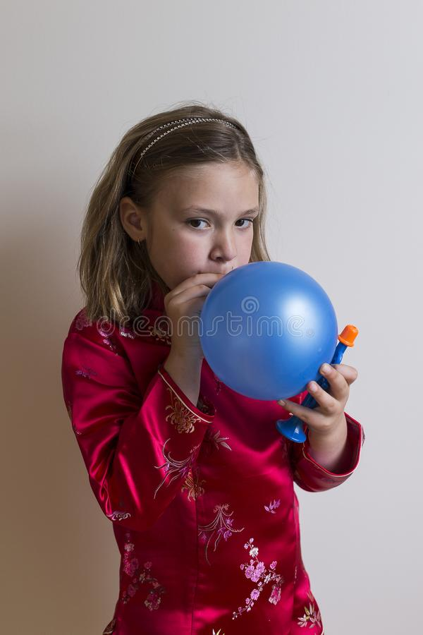 Pretty seven-year-old girl in red satin top blowing up a blue balloon. Vertical photo of pretty seven-year-old girl in red satin top blowing up a blue balloon royalty free stock photo