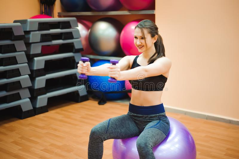 Pretty sexual straight fitness woman with musculat body lying on big ball in sport hall training indoor, horizontal. Picture royalty free stock image
