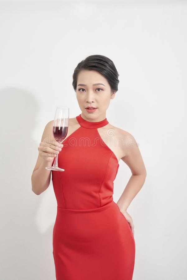 Pretty sexy asian woman on white background. Beautiful young lady in red long evening dress looking over shoulder. Glass of royalty free stock photo
