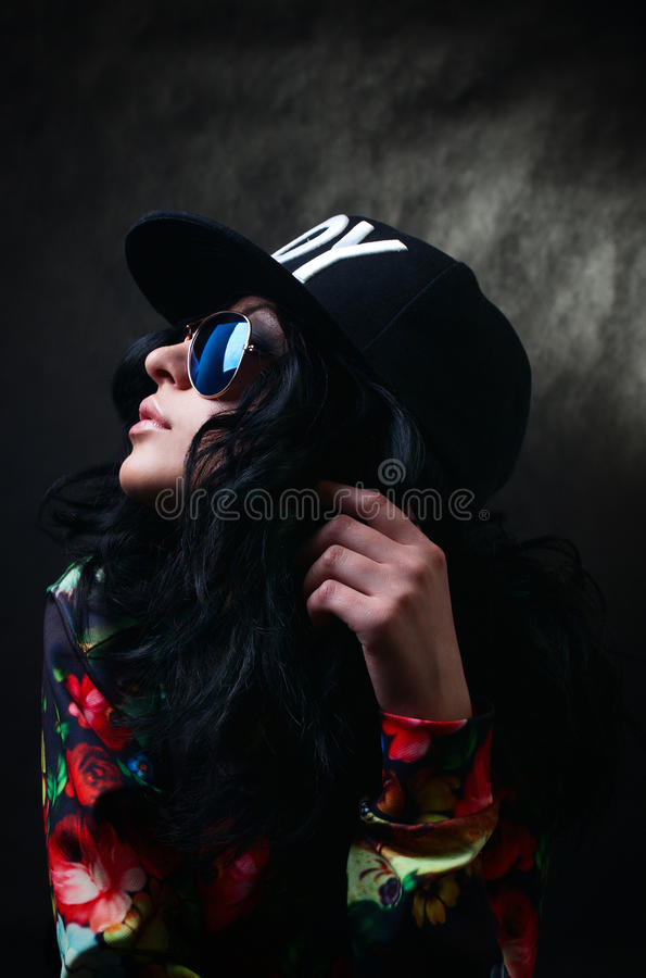 Pretty brunette in a black cap and glasses. Swag girl. Fash stock photos