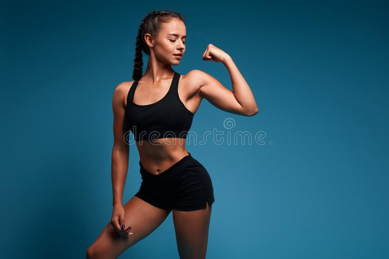 Pretty sexy slim attractive girl in fashion bra and shorts shows her biceps. Close up photo.  blue background, studio shot. copy space. strength training stock photography