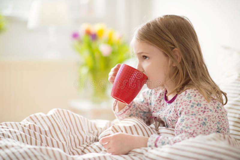 Pretty sick little child girl laying in bed drink tea royalty free stock photo