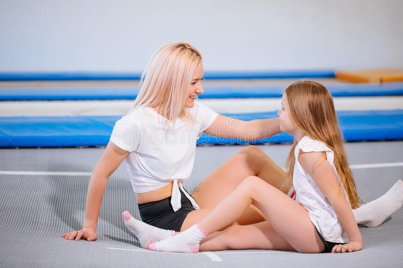Pretty siters girls having fun indoor. Jumping on trampoline in children zone royalty free stock images