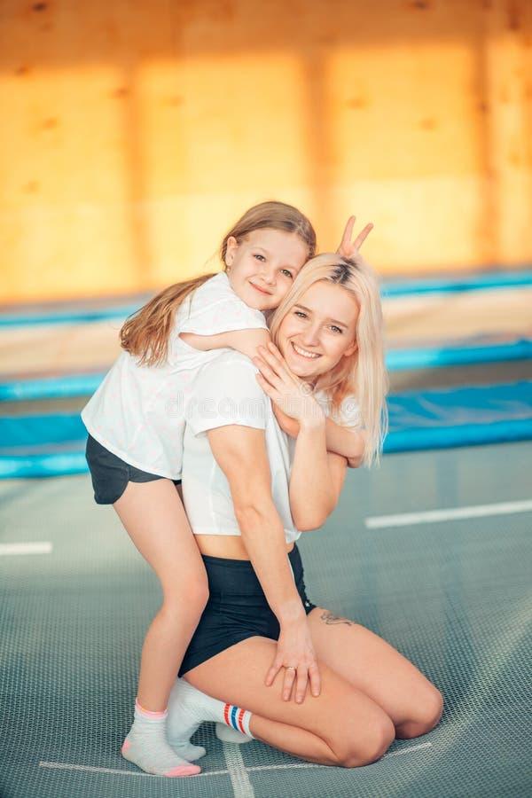 Pretty siters girls having fun indoor. Jumping on trampoline in children zone stock photo