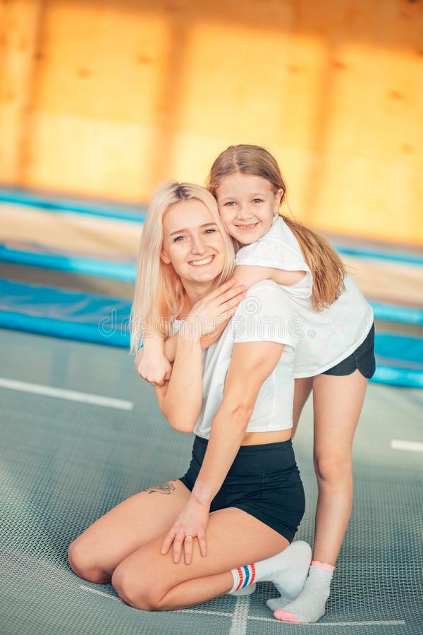 Pretty siters girls having fun indoor. Jumping on trampoline in children zone royalty free stock photo