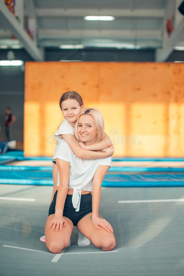 Pretty siters girls having fun indoor. Jumping on trampoline in children zone stock image
