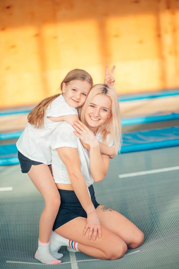 Pretty siters girls having fun indoor. Jumping on trampoline in children zone stock photography