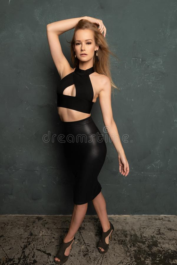 Blonde in black leather stock image