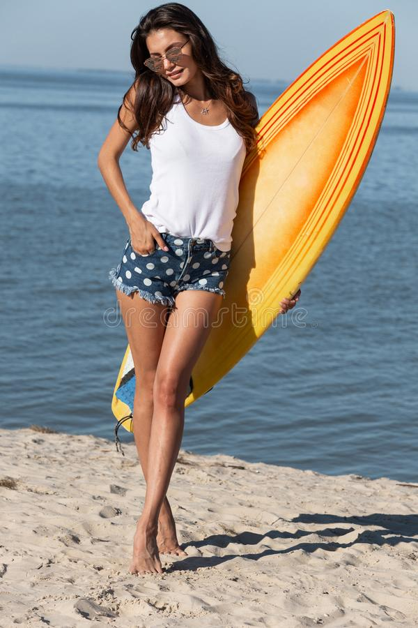 Pretty slender dark-haired girl in sunglasses dressed in a white t-shirt and jean shorts standing with a yellow royalty free stock photos