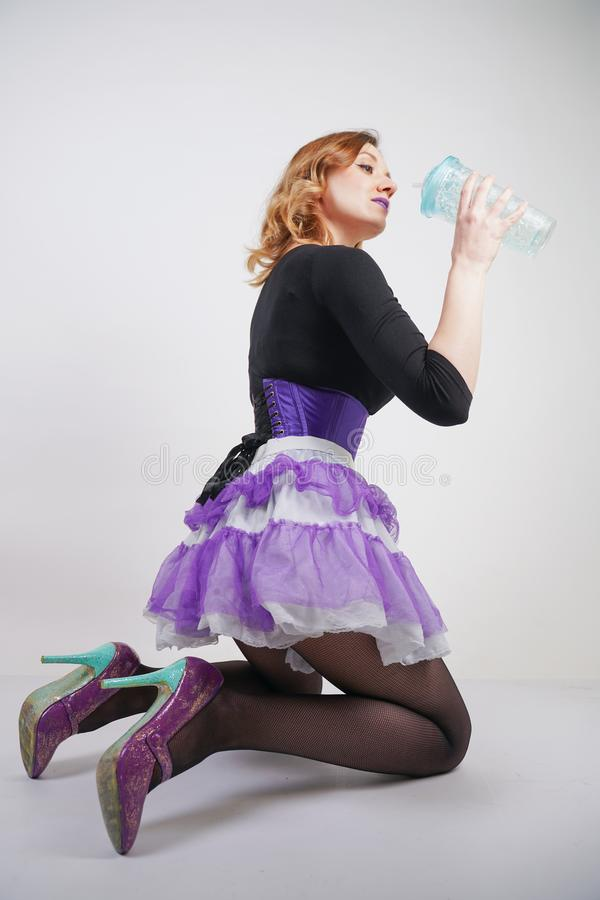 Pretty slender girl in purple corset with tutu skirt and mesh black pantyhose standing with blue glass of water on white studio ba. Ckground isolated stock photo