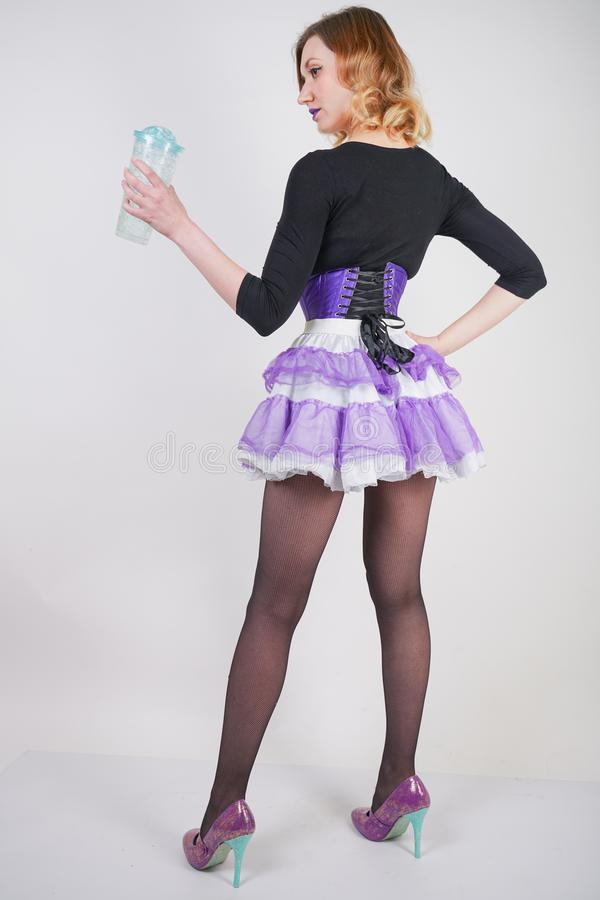 Pretty slender girl in purple corset with tutu skirt and mesh black pantyhose standing with blue glass of water on white studio ba. Ckground isolated royalty free stock photos