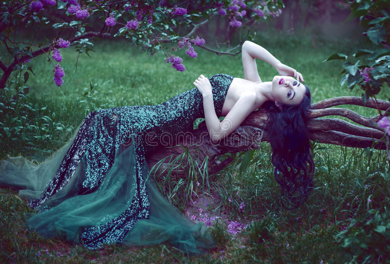 Pretty slim girl with dark hair in a long emerald green dress wi stock images