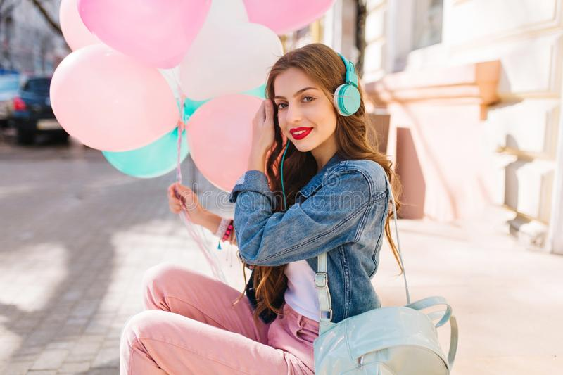 Pretty slim girl in retro outfit listening favourite song in headphones waiting for party start. Charming young woman in royalty free stock photography
