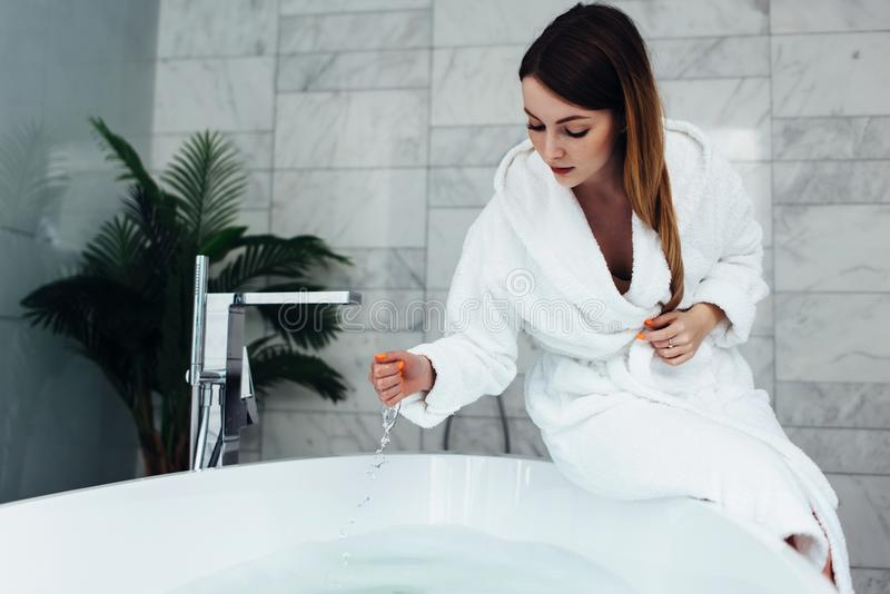 Pretty slim woman wearing bathrobe sitting on edge of bathtub filling up with water stock photo