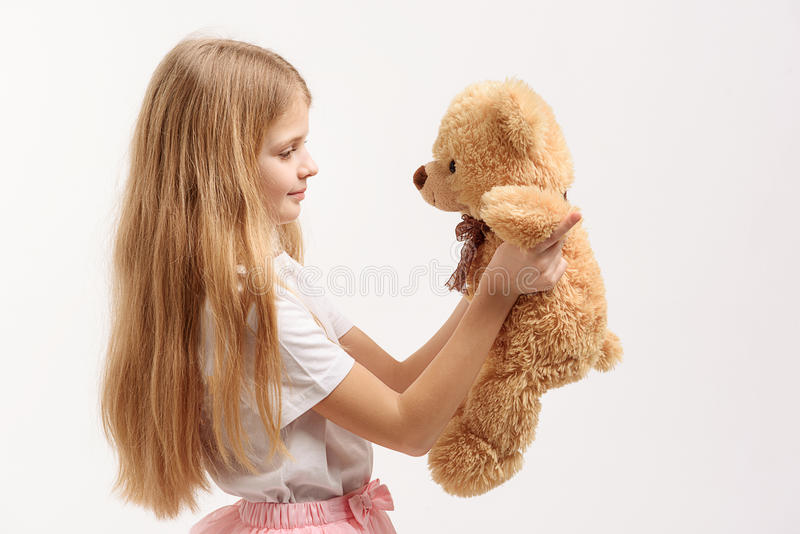 Pretty small girl holding toy. Little female kid is playing with soft toylike bear and looking at it. Isolated. Profile stock photos
