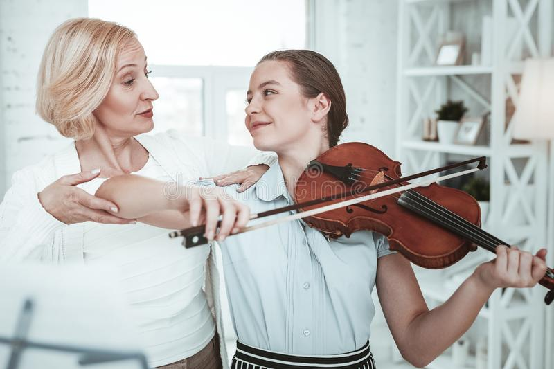 Pretty smart girl looking at her grandmother. Music family. Pretty smart girl looking at her grandmother while learning to play the violin royalty free stock photo