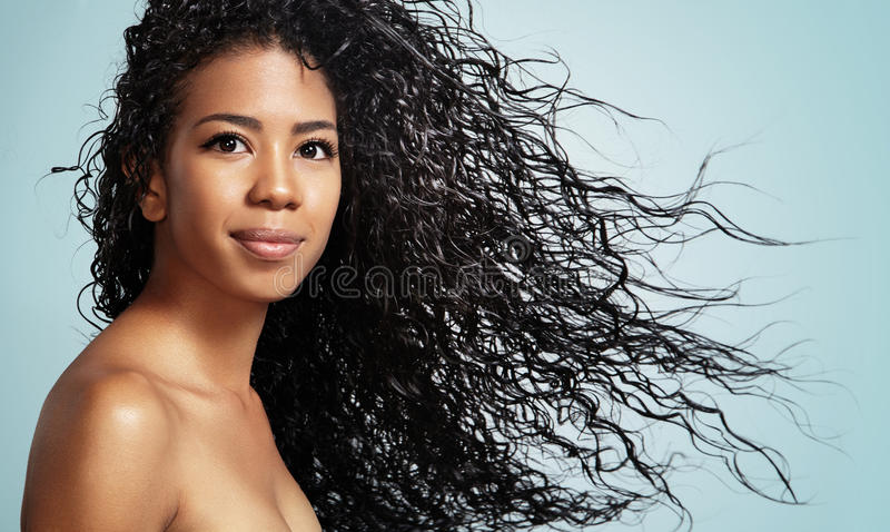 Pretty smile latin woman with curly hair. Black woman with curly hair looking at camerar royalty free stock image