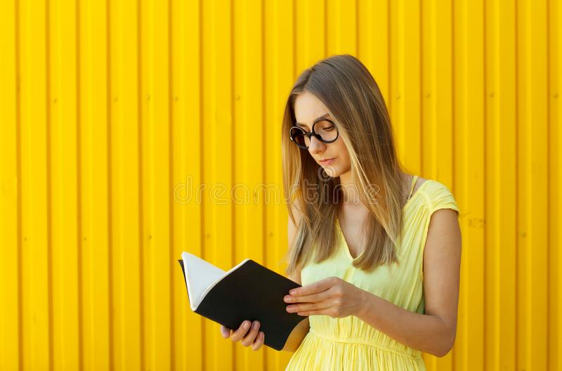Pretty smiley girl student with book wearing funny toy round glasses stock photo