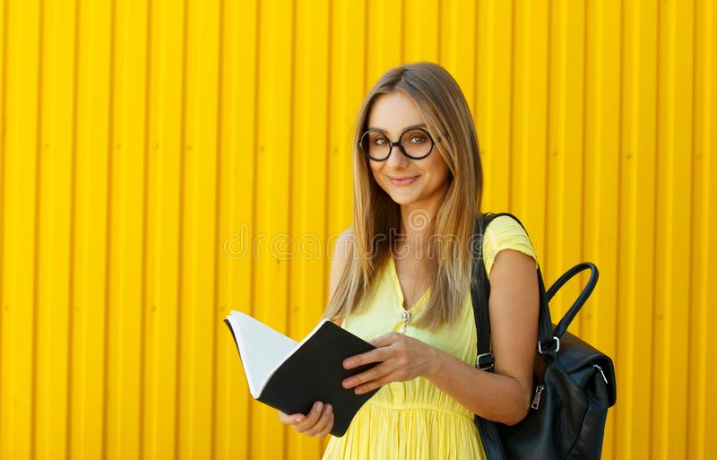 Pretty smiley girl student with book wearing funny toy round glasses and suitcase over yellow background stock photography