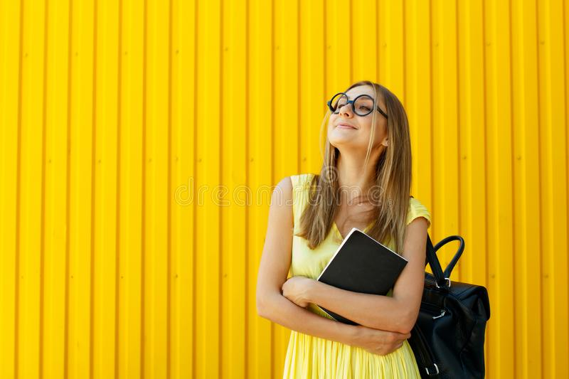 Pretty smiley girl student with book wearing funny toy round glasses and suitcase over yellow background stock photos