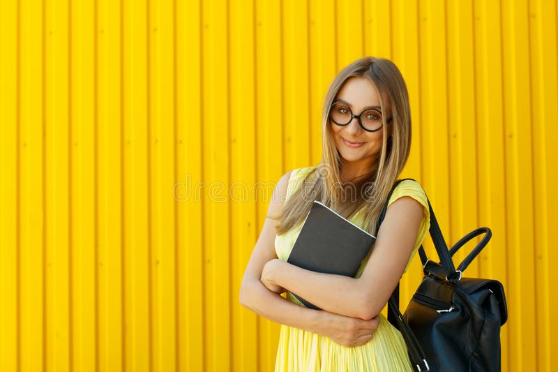 Pretty smiley girl student with book wearing funny toy round glasses and suitcase over yellow background royalty free stock images