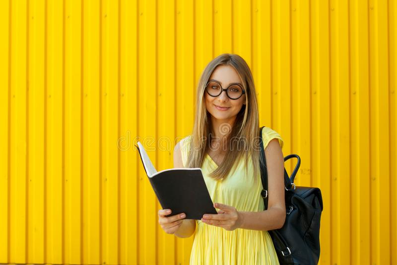 Pretty smiley girl student with book wearing funny toy round glasses and suitcase over yellow background royalty free stock photo