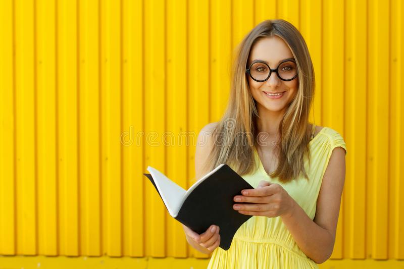 Pretty smiley girl student with book wearing funny toy round glasses over yellow background stock photos