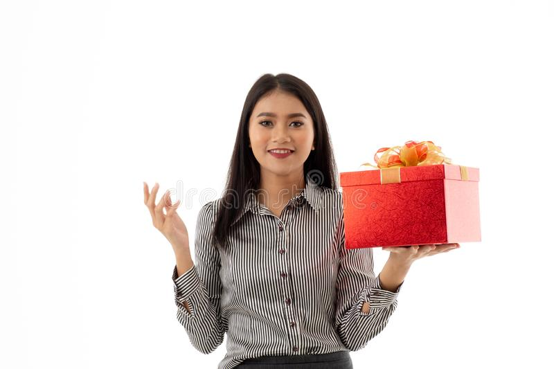 Pretty smiling asian young woman holding beautiful red present box and opening hand palm isolated on white background. Portrait of stock image