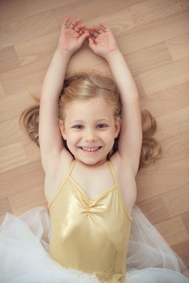 Pretty smiling ballet chilg girl in white tutu on floor stock image