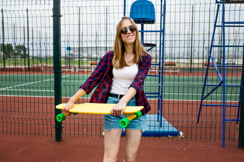 A pretty smiling blond girl wearing checkered shirt, white cap and sunglasses is walking through the sports field with a stock image