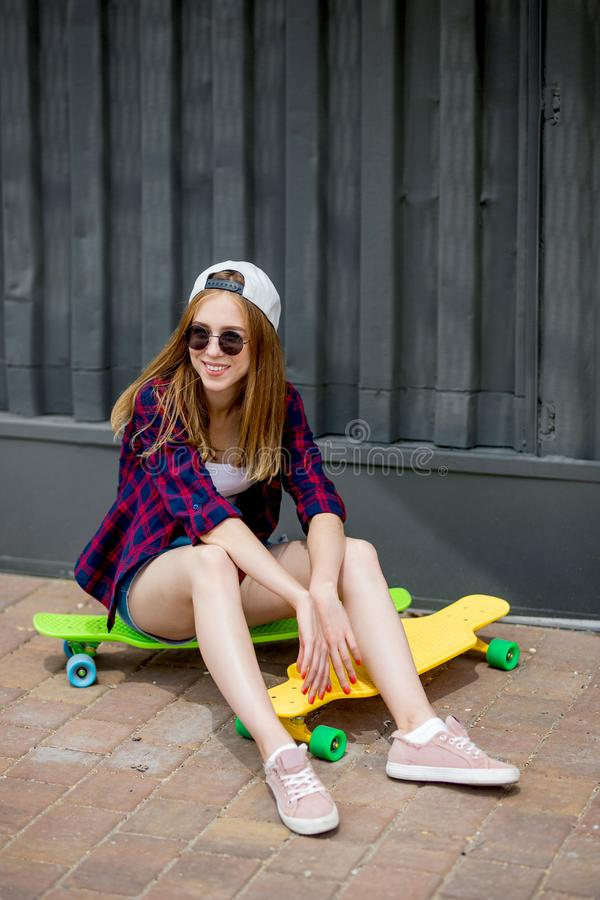A pretty smiling blond girl wearing sunglasses, checkered shirt and denim shorts is sitting on the bright logboards in stock photos