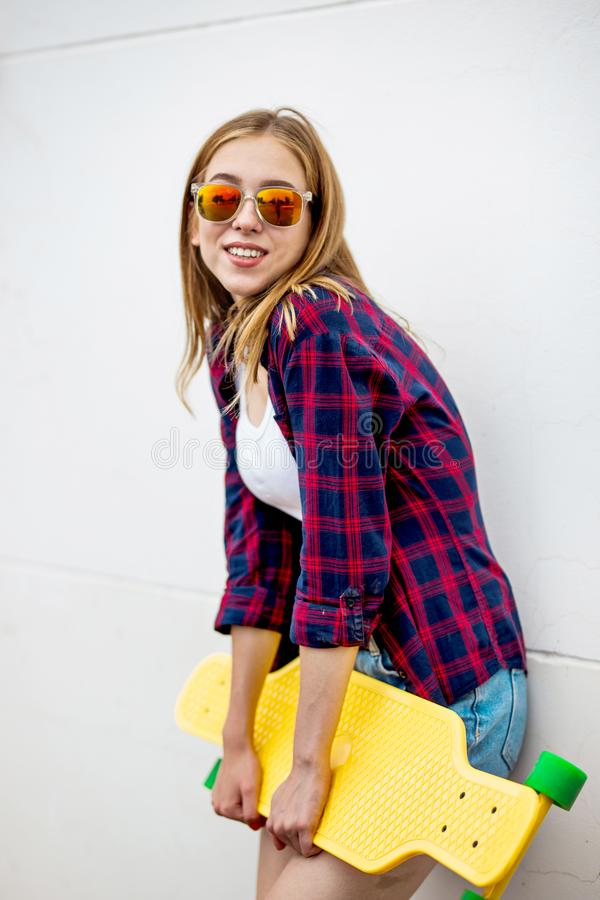 A pretty smiling blond girl wearing sunglasses, checkered shirt and denim shorts is standing in front of the gray wall stock image