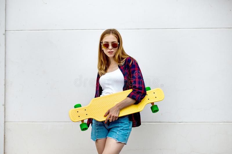 A pretty smiling blond girl wearing sunglasses, checkered shirt and denim shorts is standing in front of the gray wall royalty free stock photo