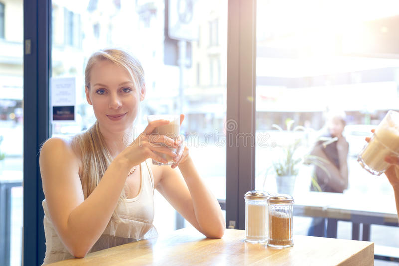 Pretty smiling blond woman in a restaurant royalty free stock images