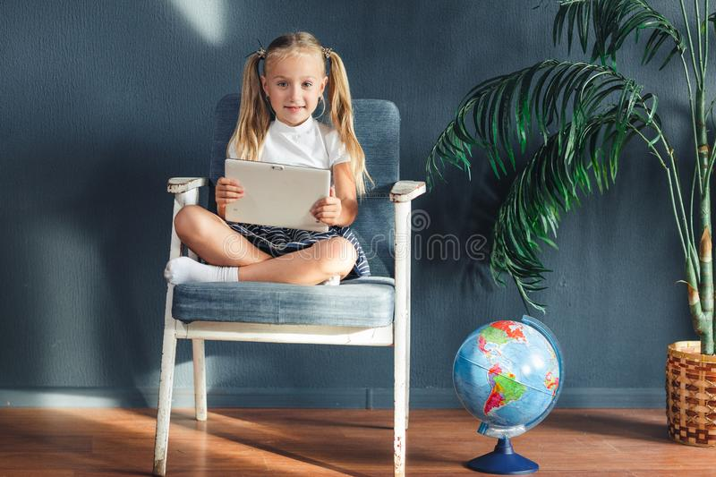 Pretty smiling blondy girl relaxing on a chair near the globe indoors at home with a tablet pc in her socks and jeans royalty free stock photos