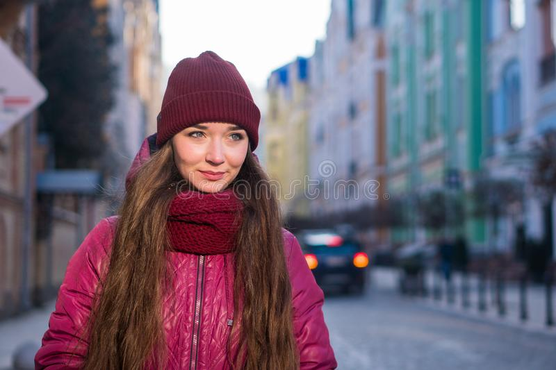 Pretty Smiling Brunette Girl Wearing Purple Winter Coat, Hat and Scarf, Walking by European Street at Winter. City Travel royalty free stock images