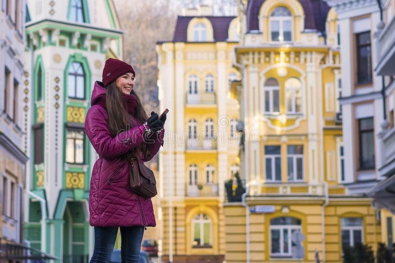 Pretty Smiling Brunette Girl Wearing Purple Winter Coat, Hat and Scarf, Walking by European Street at Winter. City Travel royalty free stock photos