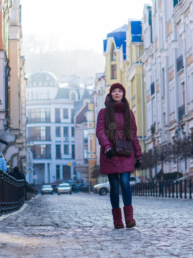 Pretty Smiling Brunette Girl Wearing Purple Winter Coat, Hat and Scarf, Walking by European Street at Winter. City Travel royalty free stock image