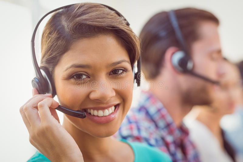 Pretty smiling businesswoman working in a call centre. Close up plan of a smiling businesswoman in a call centre royalty free stock photos